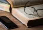 Livro, óculos e iPhone