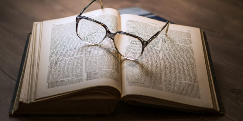 Livro e óculos sobre a mesa