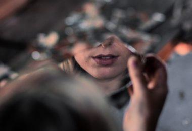 Espelho quebrado com mulher refletida