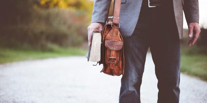 Homem na estrada com bíblia na mão