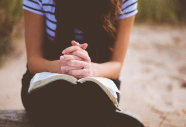 Mulher orando com a bíblia