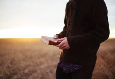 Homem no campo com a bíblia na mão