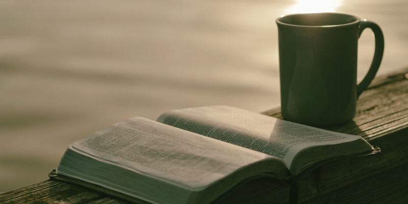 Bíblia e caneca, em frente ao lago