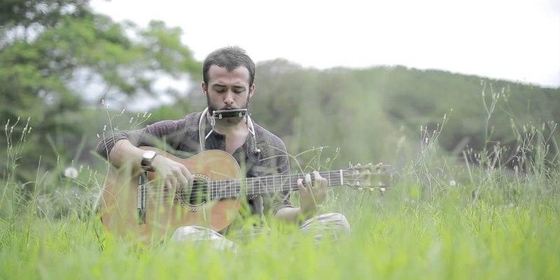 Gabriel Iglesias tocando violão e gaita