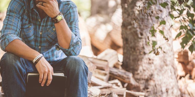 Homem sentado na floresta com a bíblia