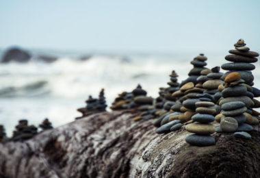 Versículos sobre paciência (imagem representando paciência - empilhamento de pequenas rochas em frente ao mar)
