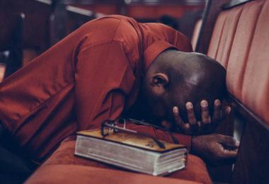 Homem ajoelhado no chão, apoiando-se no banco de uma igreja. Representa nossa lista de versículos sobre pecado.