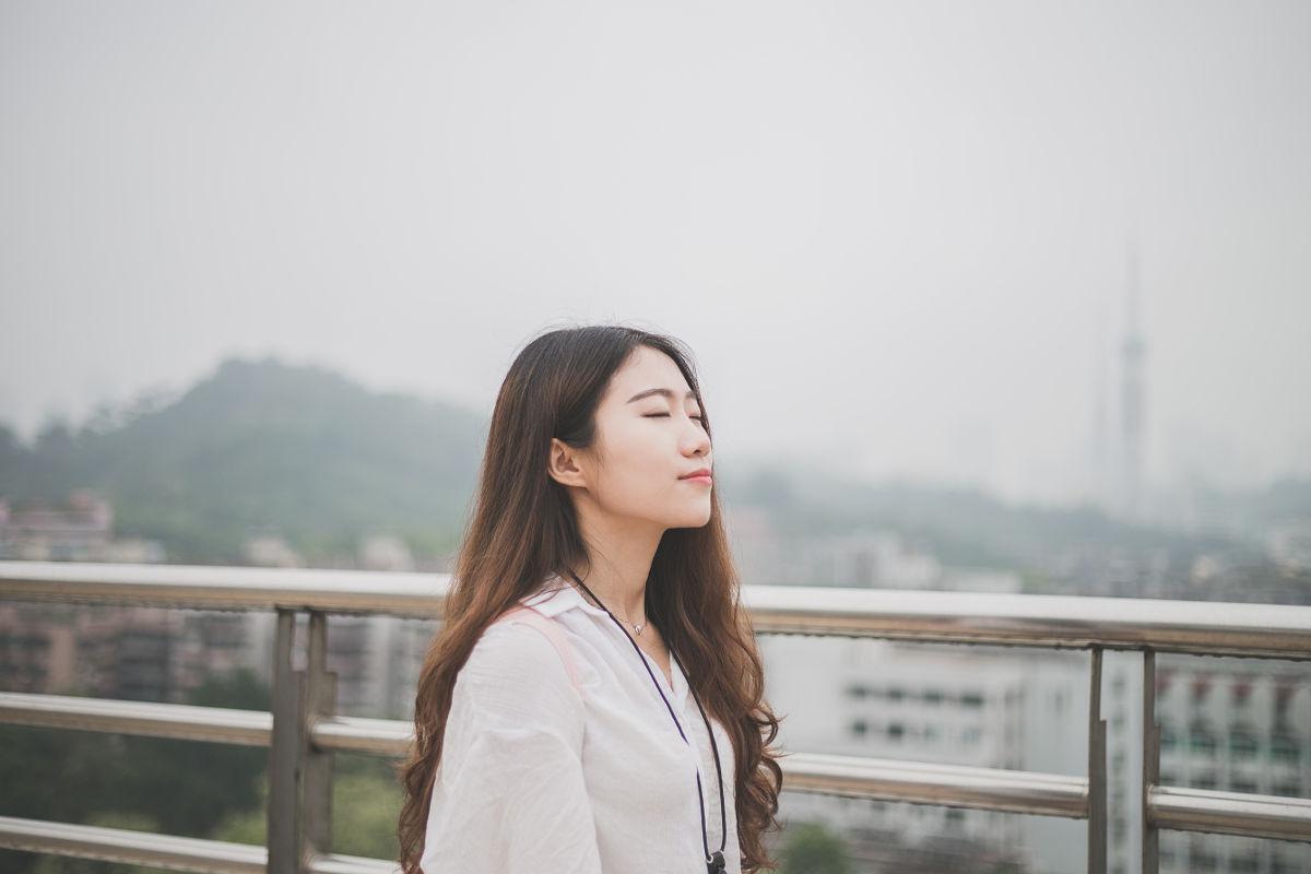 Mulher de olhos fechados representando os versículos sobre tranquilidade