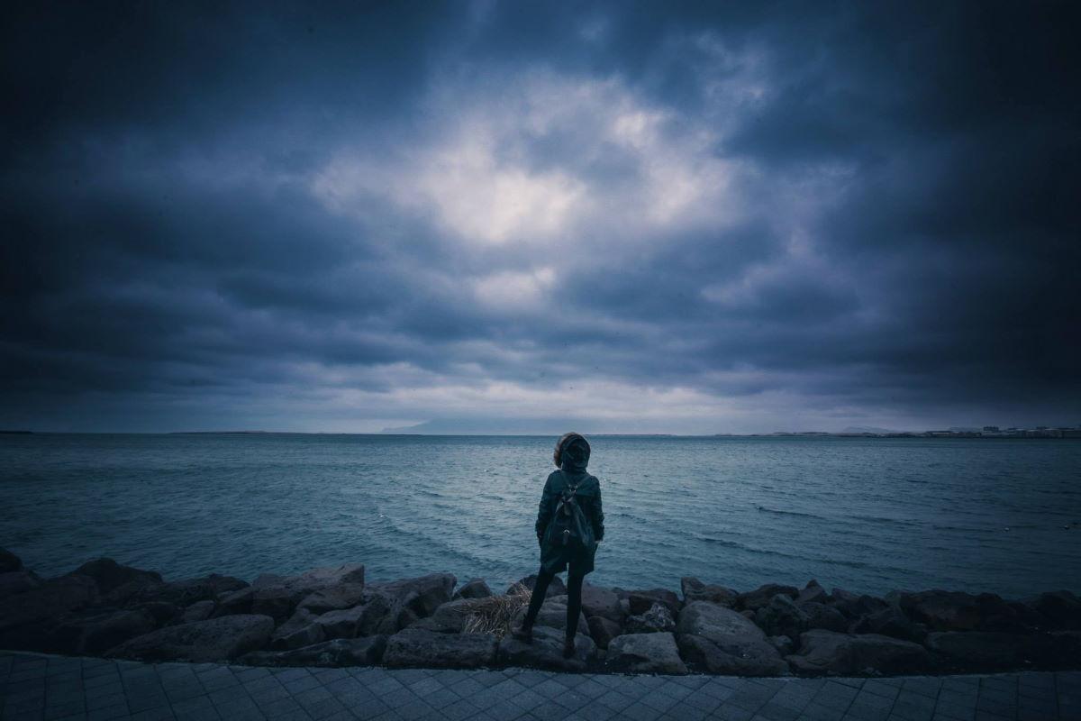 Pessoa parada em frente ao mar representando os versículos para pessoas desanimadas