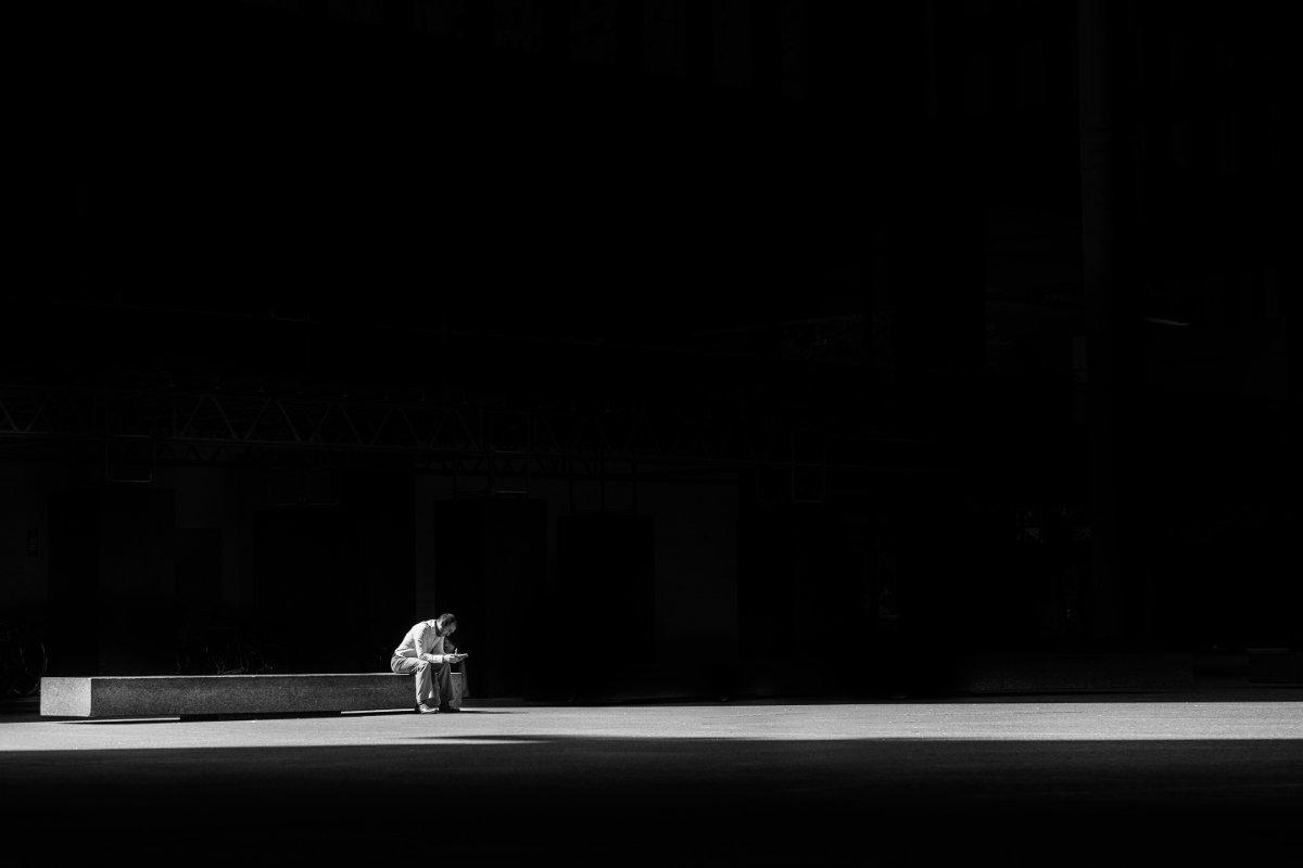Homem sentado, fundo preto - representando os versículos sobre doenças