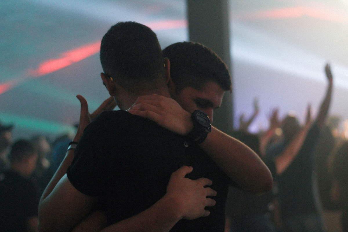Amigos abraçados num culto