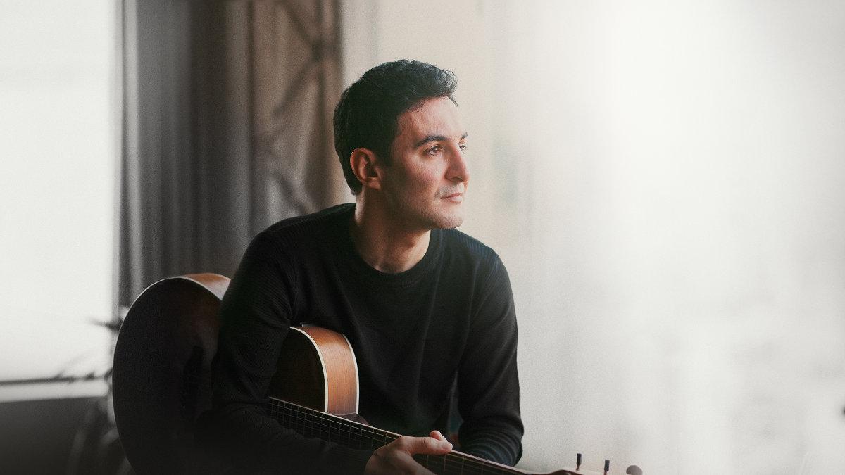 Cantor Leandro Borges com violão na mão. Release de sua música Saudade