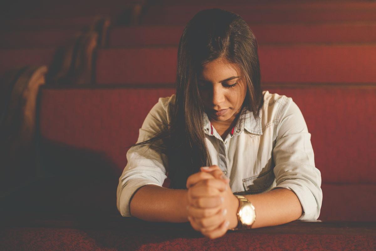 Mulher orando em igreja, representando o versículo Orai sem cessar