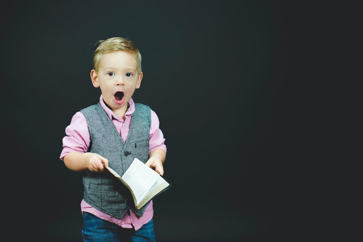 Criança com a bíblia na mão representando os versículos para ler com as crianças