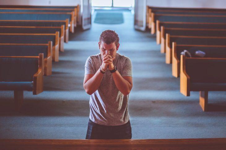 Homem orando em igreja representando as orações da bíblia