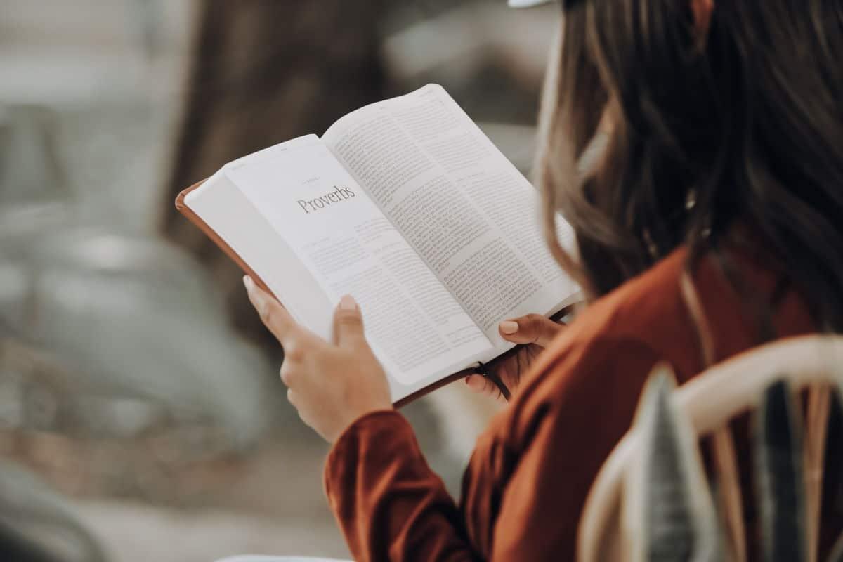 Mulher de costas lendo a bíblia