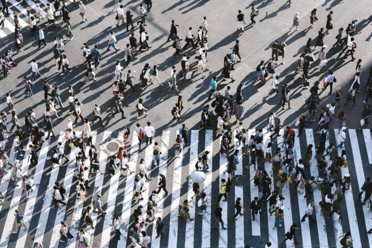 Pessoas cruzando uma rua representando a mensagem bíblica - discípulos e multidão