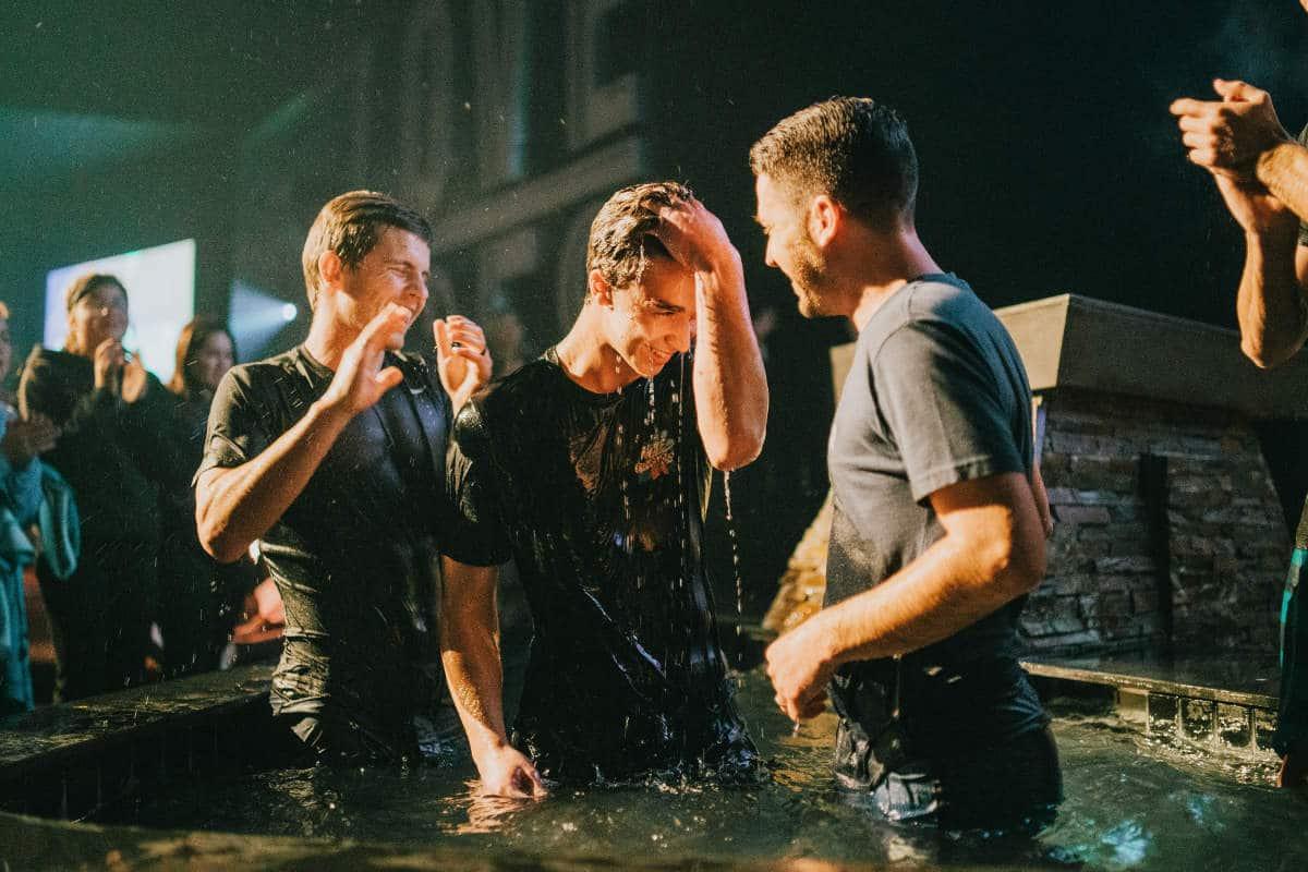 Jovem sendo batizado, representando os versículos sobre batismo