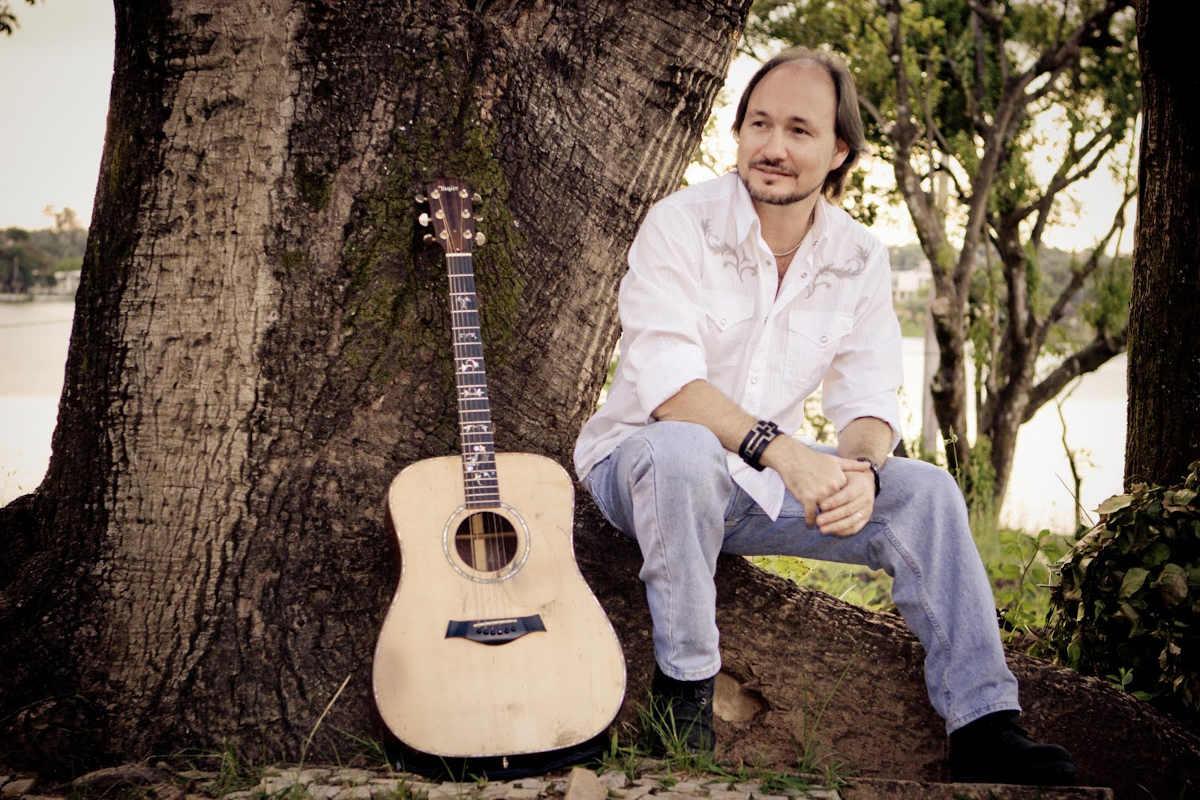 David Quinlan sentado na árvore com seu violão ao lado