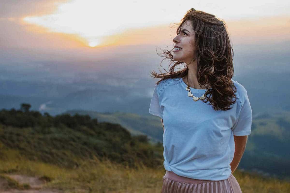 Rachel Novaes numa foto com o pôr-do-sol de fundo