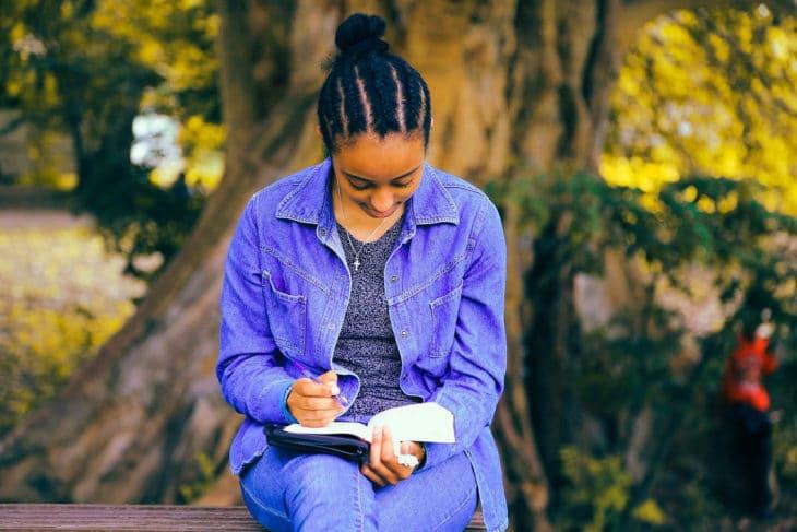 Mulher sentada num banco com a bíblia, representando o estudo de Provérbios completo e gratuito