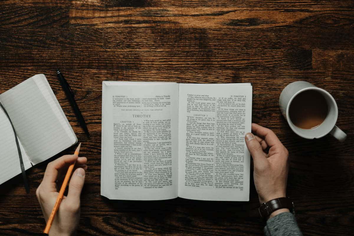 Bíblia, caderno de anotações e caneca de café sobre a mesa