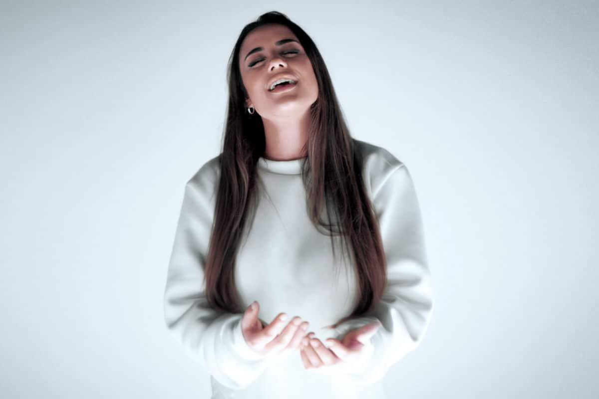 Capa do Single Sua Paz, de Isadora Pompeo. Na foto, ela está sozinha, cantando, ao centro. Vestida com um moletom branco, de olhos fechados e mãos à frente do corpo, na altura do abodômem.