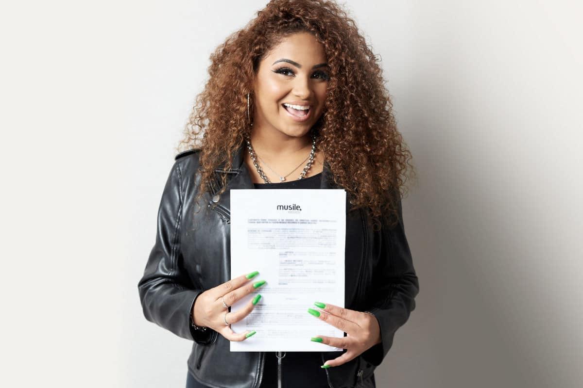 Cantora Sarah Beatriz segurando seu contrato com a Musile